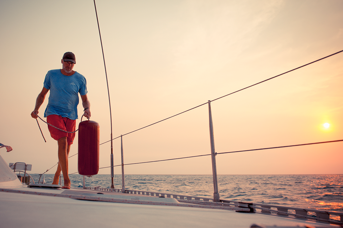 Red boat fender with sailor on a catamaran at sunset, and Polyform HTM Series boat size chart.HTM Series Fenders Classic Red